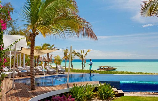 man walks next to infinity pool on thanda island. Sun loungers are lined up, along with palm trees and bright blue ocean in background