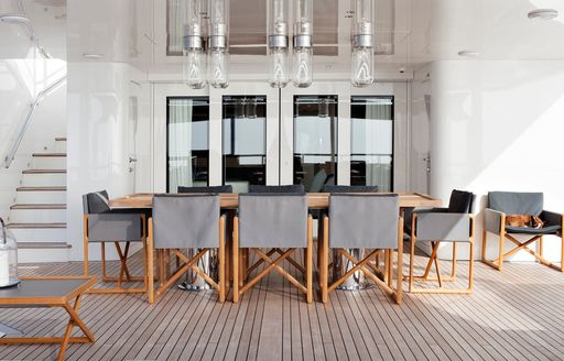 Grey chairs surround a light wood table on the exterior of a superyacht
