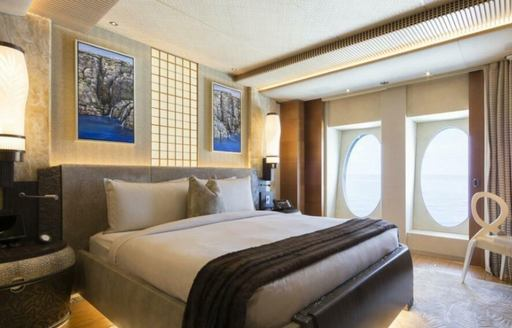 Double guest cabin onboard yacht charter NIRVANA. Central double berth with bedside tables and a dressing table next to window.