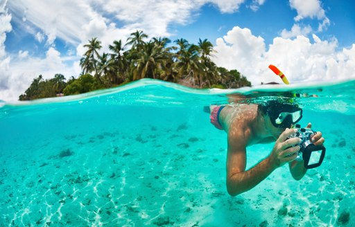 snorkeller takes pictures of the colourful underwater world in the Maldives
