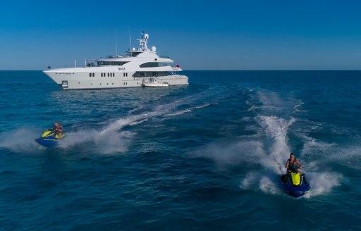 Two jet skis speeding away from Superyacht BACA