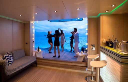 friends aboard a superyacht dance on a swim platform as beach club is set up for a party