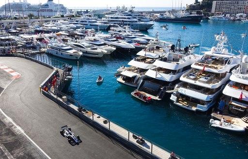 Row of superyachts moored at Monaco Grand Prix, F1 car speeding past on track adjacent to marina.