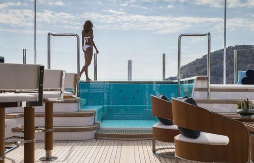 A charter guest approaches the Jacuzzi featured on board superyacht AQUILA