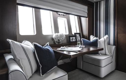 two armchairs and table form seating area in the master suite on board charter yacht CRISTOBAL