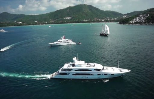 A collection of superyachts cruising close to the Kata Rocks Resort in Phuket, Thailand