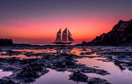 LAMIMA yacht below sunset