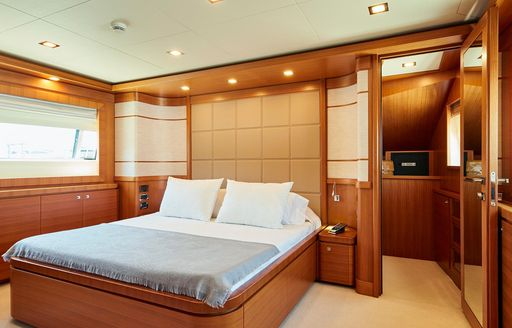 master suite with warm woods and central bed on board motor yacht DEVA