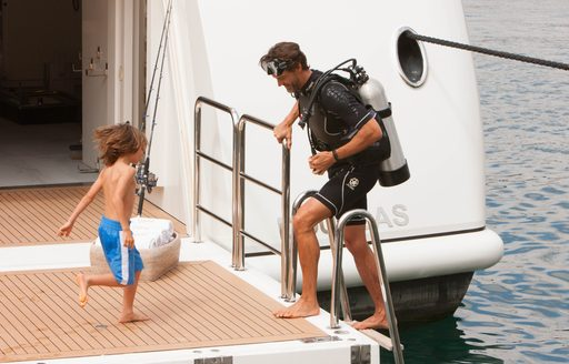 man teaches child how to use water toy on benetti superyacht st david