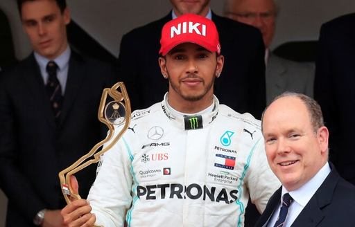 Lewis Hamilton winning the Monaco Grand Prix in the South of France, accepting his trophy and wearing red cap with 'Niki' written on it