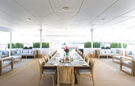 long dining table with cosy lounging options on main aft deck of superyacht 'Indian Empress'