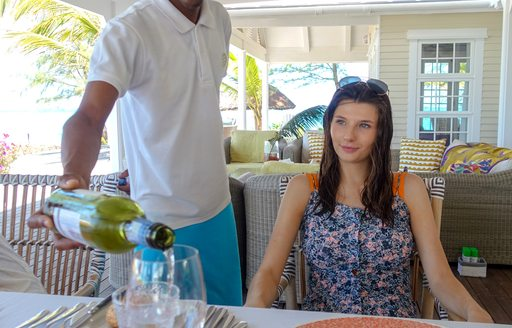 waiter pours drink for woman on thanda island