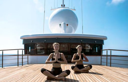 Couple doing yoga in open air on deck of Superyacht CHAKRA