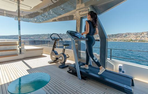 Charter guest using a treadmill onboard Ferretti yacht charter 30m PENELOPE, exercise bicycle adjacent, surrounded by sea