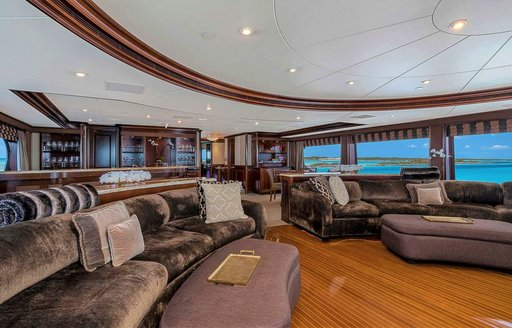 Interior details of luxury motor yacht, with sofa seating and views over Caribbean