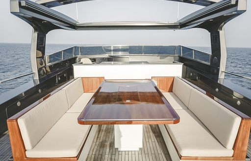 seating area with table on the sundeck of luxury yacht Timeless