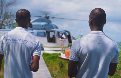 staff wait to give cocktails to guests arriving via helicopter on thanda island