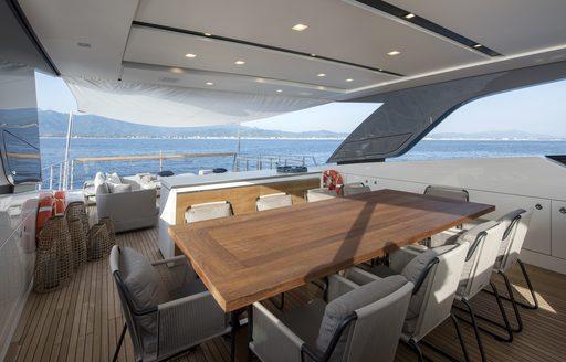 al fresco dining table on the flybridge of charter yacht DINAIA