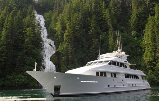serenity yacht next to waterfall in norway