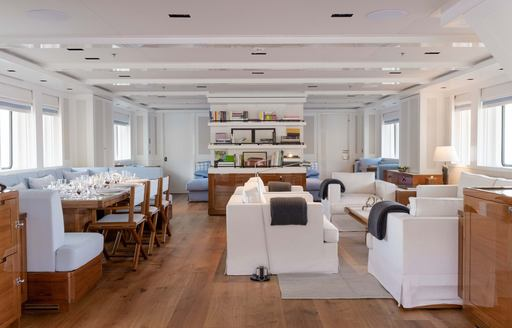 Open plan interior with sofas and dining table on explorer yacht 'Blue II'