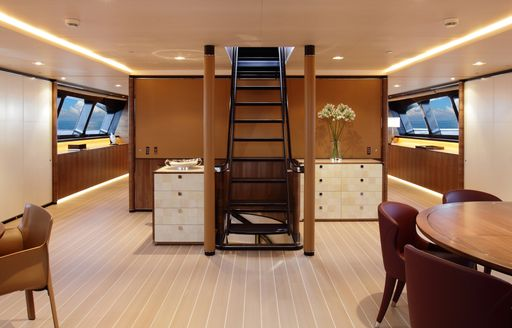 dining area and steal and wenge staircase in the forward section of luxury yacht FIDELIS