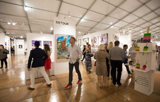 Visitors walking round exhibit in Art Basel Miami gallery, paintings on display around the room.