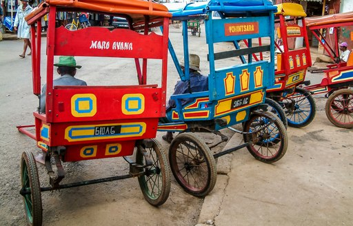 A red and a blue pedal taxi seen from behind
