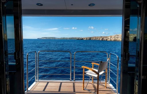Luxury charter yacht ANYA unfolding sea terraces, with chair overlooking the ocean