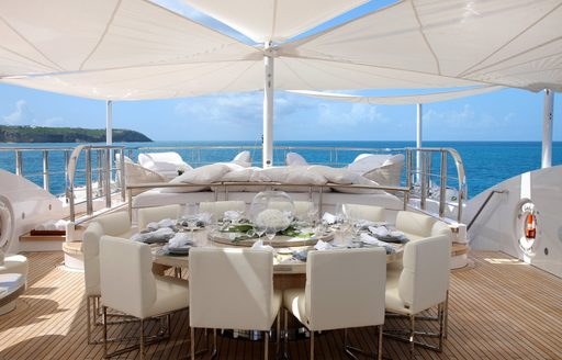circular alfresco dining table under shade of awnings on sundeck of superyacht 'Lady Luck'