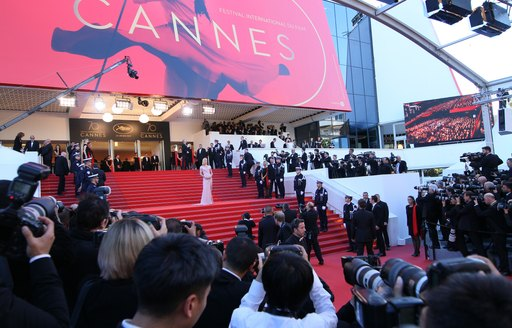 Steps covered by red carpet leading to Cannes Film Festival venue- the Palais des Festivals- with superyachts in background
