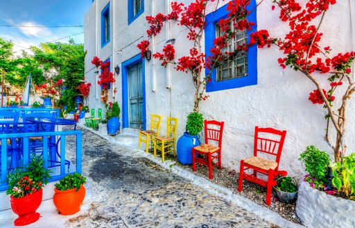 cobbled streets and blue and white taverna with red flowers growing across the plaster wall