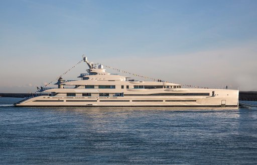 Benetti's motor yacht LANA as she cruises the waters of the Caribbean at dusk with her guests celebrating on the beach cl;ub