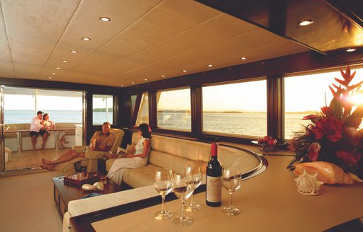 charter guests enjoy a glass of wine in skylounge of motor yacht 'Emerald Lady'