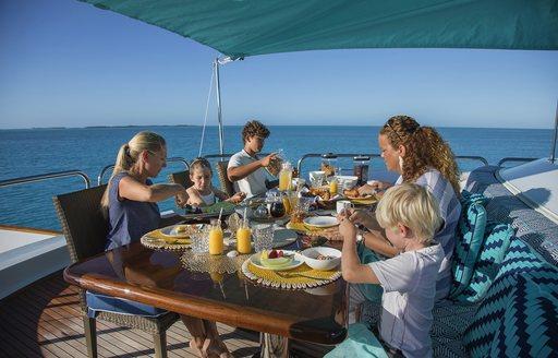 charter guests enjoy breakfast on portugese bridge of superyacht sweet escape