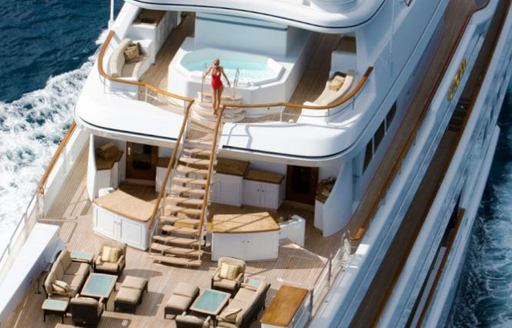 Aerial image of woman alighting steps on superyacht UTOPIA, which lead to aft deck seating