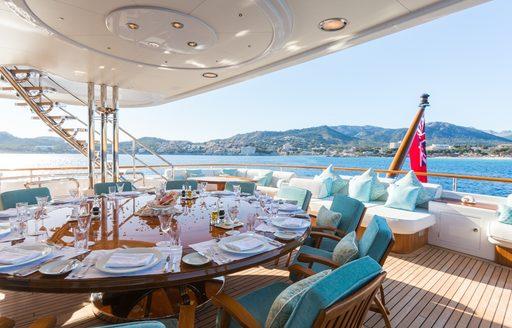 sophisticated alfresco dining setup on upper deck aft of charter yacht CALLISTO