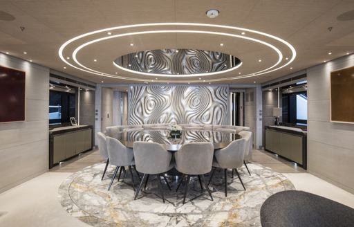 dining set up on superyacht severins, with marble flooring and light on ceiling