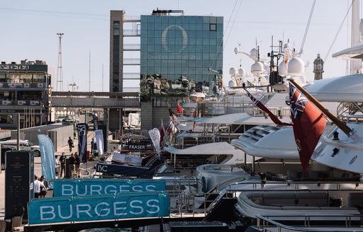 superyachts lined up decorated in brokerages' bunting in OneOcean Port Vell for The Superyacht Show