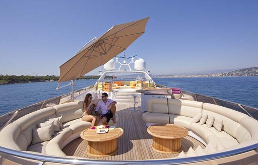 luxury charter yacht daloli, sundeck with circle seating and coffee tables and umbrellas