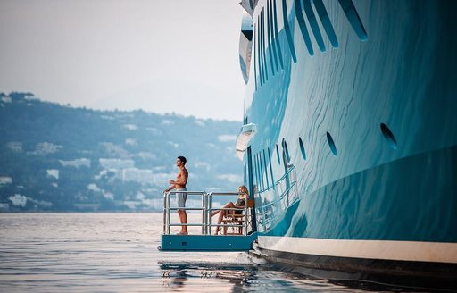 Charter guest stands on side balcony on board luxury yacht