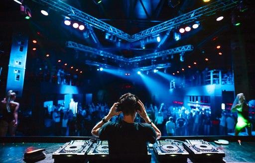 DJ holding headphones in front of mixing decks at Monaco Grand Prix