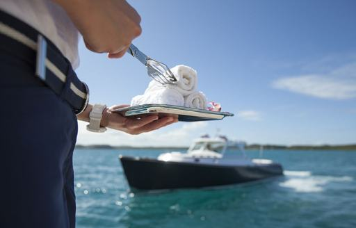 Crew member of yacht hands out hot towels to guests as they arrive back to the yacht on a tender
