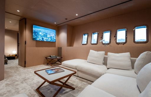 Sofa and table with TV on wall of charter yacht NEOPRENE