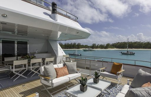 al fresco dining table and seating area on upper deck aft of luxury yacht M3