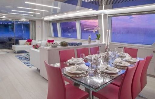 interior dining area with stainless steel table and bright pink chairs on board superyacht Alandrea