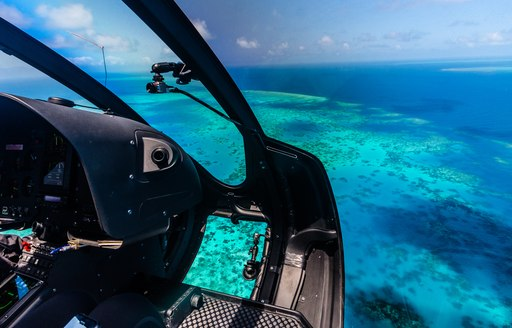 A helicopter flies over the Great Barrier Reef