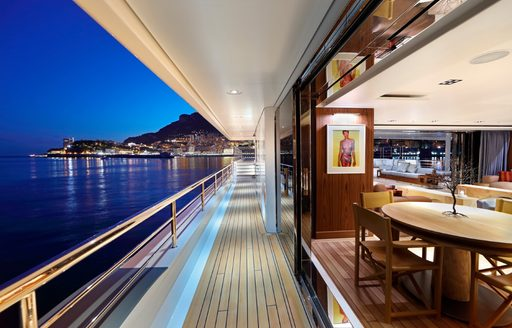 a side deck looking into a salon and out across the water on board expedition yacht Planet Nine