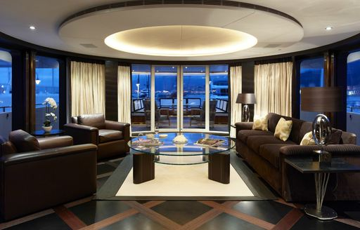 deep brown armchairs and sofas flanked by full-length windows in the skylounge aboard luxury yacht ROCKET