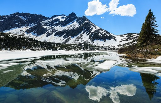 snow covered mountains reflected in the water in Alaska