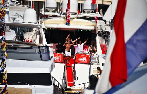 Group of charter guests onboard motoryacht, cheering and celebrating at Monaco Grand Prix.